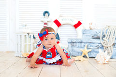 Little sailor traveler sits on the background of an anchor and a circle Royalty Free Stock Images