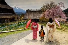 Little samurai boy with sword and Two Kimono Japanese women. At Saiko Iyashi no Sato Nenba, former farming, village near Mountain Fuji, Japan. Preserved wooden royalty free stock photos