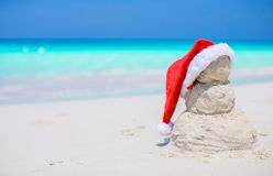 Little sandy snowman with red Santa Hat on white. Beach royalty free stock photo