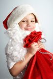 Little santa. Small boy with santa's hat and bag full of gifts Stock Photos