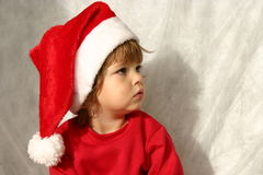 Little Santa. Kid wearing Santa's hat lost in thoughts Royalty Free Stock Photo