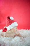 Little Santa. Baby girl on red background Royalty Free Stock Photo