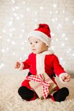 Little Santa baby over defocused lights wall royalty free stock images