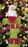 Little santa baby seated on presents Royalty Free Stock Photo