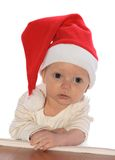 Little Santa Claus. Baby in the christmas cap on the table Royalty Free Stock Image