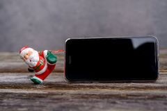 Little Santa Claus pulling  big smartphone Stock Photo