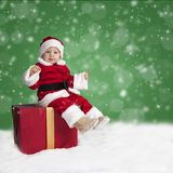 Little santa claus seated on a Christmas present in the snow Stock Images