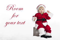 Little santa claus seated on a Christmas in the snow Stock Photography