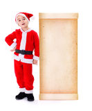 Little Santa Claus standing near big old paper wish list Stock Image