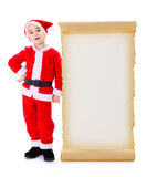 Little Santa Claus standing near big wish list. Little Santa Claus boy, standing near big blank wish list Stock Images