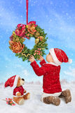 Little Santa, decorates Christmas wreath. Child, dressed as Santa Claus, decorates Christmas wreath stock photography
