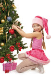 Little santa girl. Decorating the christmas tree Stock Photos