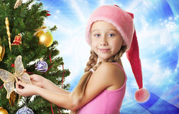Little santa girl. Decorating the christmas tree Stock Photo