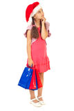 Little santa girl with bags looking up. Little girl wearing Santa hat holding shopping bags and looking up to copy space isolated on white background Royalty Free Stock Image