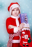 Little Santa. Holds a gift in hand Stock Photos