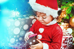 Little santa kid checking the gift. Little santa girl checking the gift Royalty Free Stock Photo