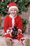 Little Santa. Sits under a fir-tree Stock Photography
