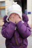 Little scared. Girl hiding face Stock Photo