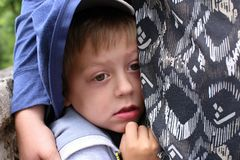 Little scared boy hidden under mom`s shirt. Small scared boy hidden under the mammy`s shirt Royalty Free Stock Photos