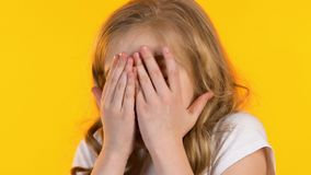 Little scared girl closing face with hands and peeking through fingers, phobia. Stock footage stock footage