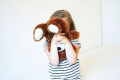 Little scared kid hiding behind teddy bear Stock Images
