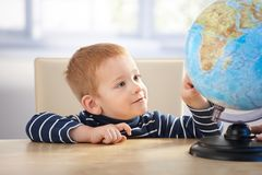 Little scholar studying globe smiling Stock Image