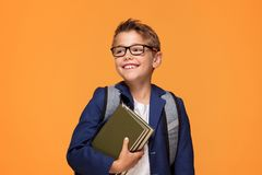 Little school boy with backpack and books. Little school boy in eyeglasses with backpack standing over orange background, holding books, smiling Royalty Free Stock Photo