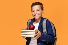 Little school boy with backpack and books. Little school boy with backpack standing over orange background, holding books and an apple, smiling Stock Photos