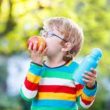Little school boy with books, apple and drink bottle. Happy little boy with books, apple and drink bottle on his first day to elementary school or nursery Royalty Free Stock Photography