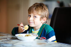 Little school boy eating pasta indoor in a canteen. Adorable little school boy eating pasta indoor. Blond child in domestic kitchen or in school canteen Cute Stock Photos