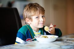 Little school boy eating pasta indoor in a canteen. Adorable little school boy eating pasta indoor. Blond child in domestic kitchen or in school canteen Cute Royalty Free Stock Photos