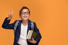 Little school boy with backpack and books. Little school boy in eyeglasses with backpack standing over orange background, holding book, smiling Royalty Free Stock Images