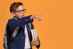 Little school boy with backpack and books. Little school boy in eyeglasses with backpack standing over orange background, holding books, smiling Stock Photography
