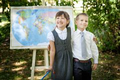 Little school children. Back to school. Little school boy and girl in a uniform with a world map with russian letters and pointer. Back to school outdoors Royalty Free Stock Photography