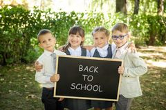 Little school children. Back to school. Little school children in a uniform with a chalkboard. Back to school outdoors Royalty Free Stock Photo