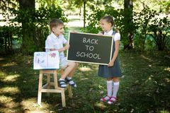 Little school children. Back to school. Little school children in a uniform with a chalkboard. Back to school outdoors Royalty Free Stock Photos
