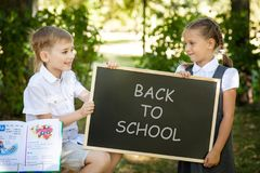 Little school children. Back to school. Little school children in a uniform with a chalkboard. Back to school outdoors Royalty Free Stock Image