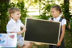 Little school children. Back to school. Little school children in a uniform with a chalkboard. Back to school outdoors. Place for text Royalty Free Stock Photos