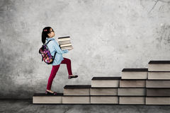 Little school girl carrying books Royalty Free Stock Image