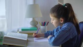 Little school girl chewing pen and counting on fingers while doing her homework stock video footage