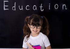 Little school girl in classroom. School kid holding supplies royalty free stock photo