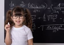 Little school girl in classroom. Genius kid. Studying kid. Pupil with glasses near black blackboard. Studio shoot, Cute kid back to school. Little girl with royalty free stock photography