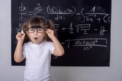 Little school girl in classroom. Smart kid. Studying kid. Pupil with glasses near black blackboard. Studio shoot, Cute kid back to school. Little girl with stock images