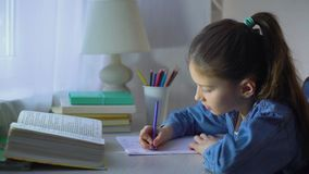 Little school girl counting on fingers while doing her homework stock video footage