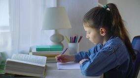 Little school girl doing homework at the table stock video footage