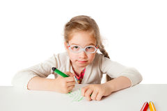 The little school-girl draws on white papper. At the table, isolated on white background stock photo