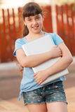 Little School Girl With Laptop. Cute Little School Girl Hugs Laptop Royalty Free Stock Photo