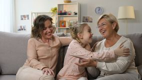 Little school girl laughing with mother and granny, family having fun together stock video footage