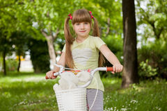 Little school-girl rides  bike in the park Stock Photos