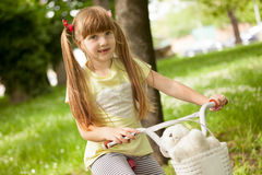 Little school-girl rides  bike in the park Stock Images